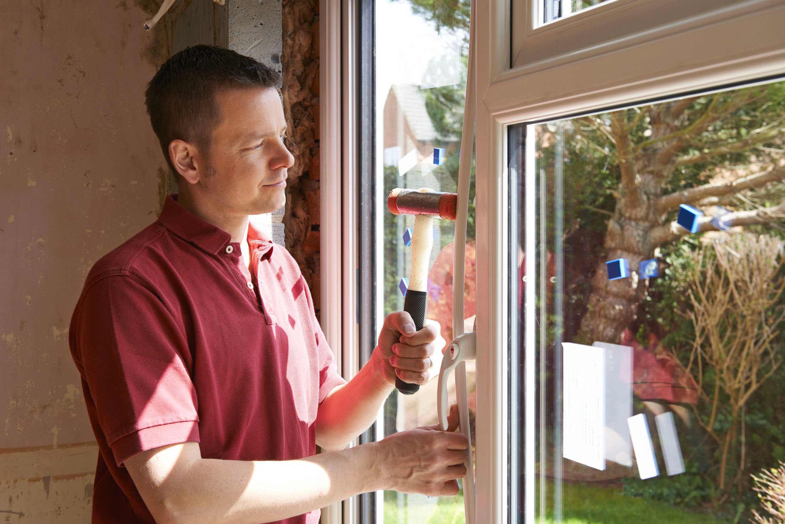 Man with a hammer fixing a window